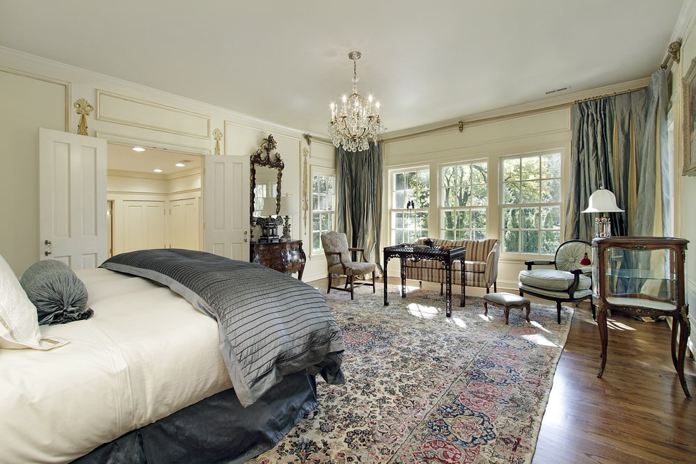 Natural light streams in through the white framed windows in this primary bedroom with a French door and natural hardwood flooring topped by a classic area rug. It showcases a comfy bed and a seating area illuminated by a crystal chandelier.