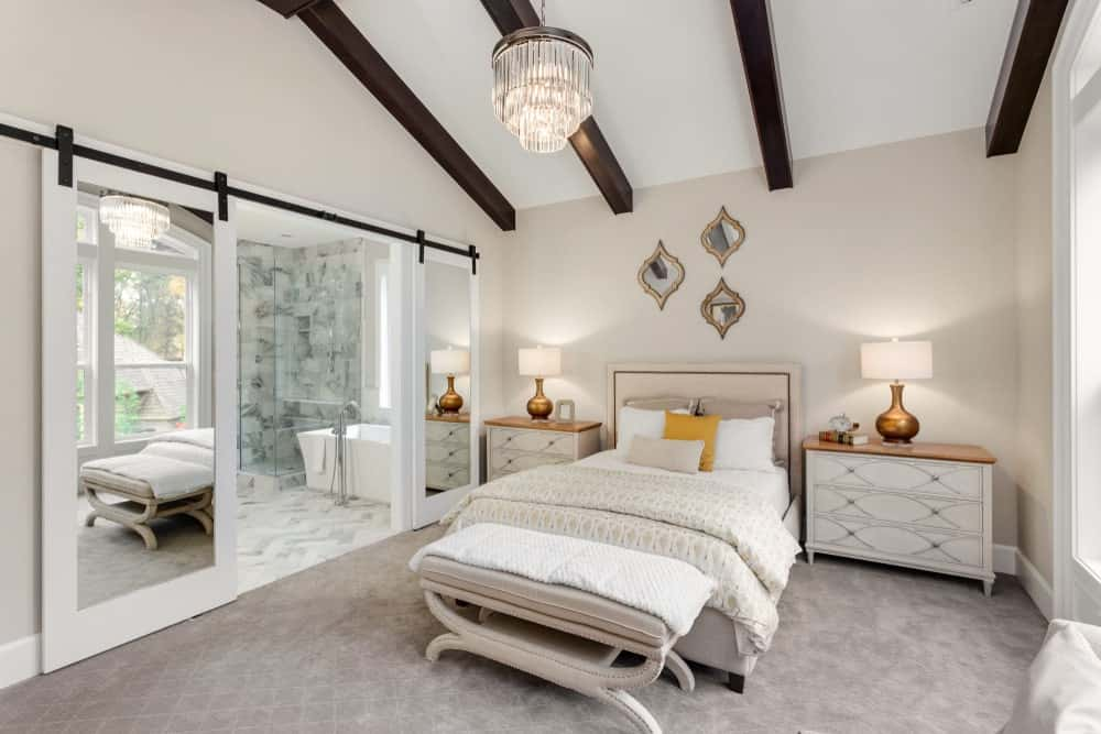 Dark wood beams add a striking contrast in this neutral primary bedroom with velvet carpet flooring and mirrored sliding doors that open to the primary bathroom. It is decorated with a cascading chandelier and stylish mirrors fixed above the beige upholstered bed.