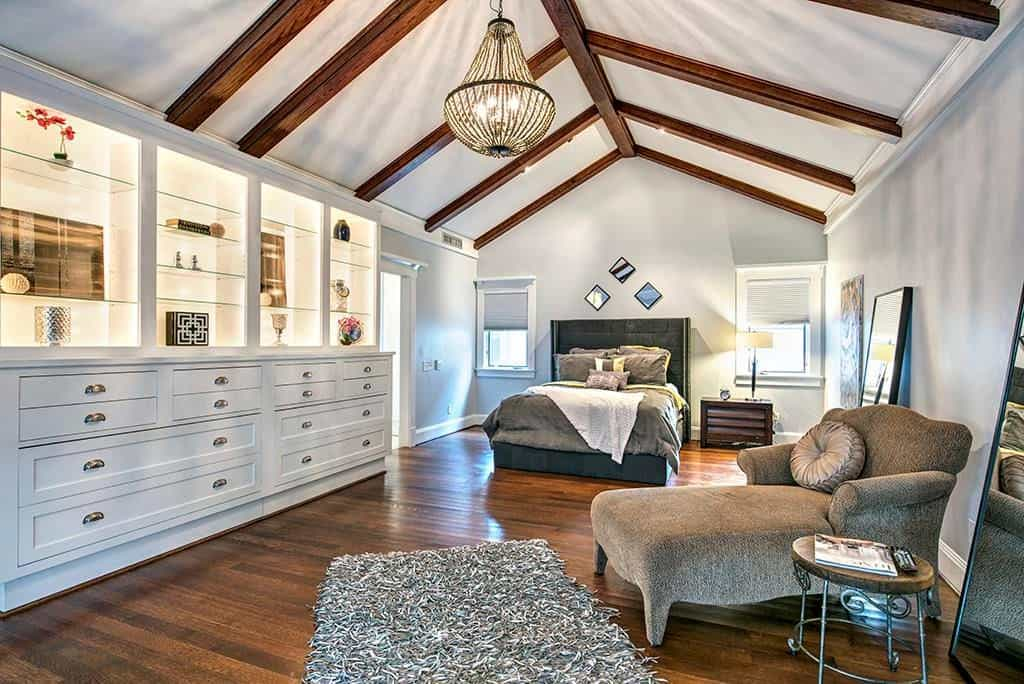 A cozy primary bedroom with a cathedral ceiling lined with exposed wood beams matching with the hardwood flooring that's topped by a shaggy rug. It includes a gray wingback bed and a classy chaise lounge that faces the built-in cabinet.