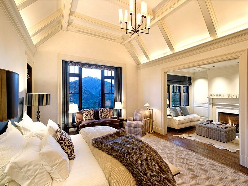 This primary bedroom offers multiple seating areas and a spectacular mountain view through the aluminum framed window. It is lighted by a glass chandelier that hung from the tall ceiling with exposed beams.