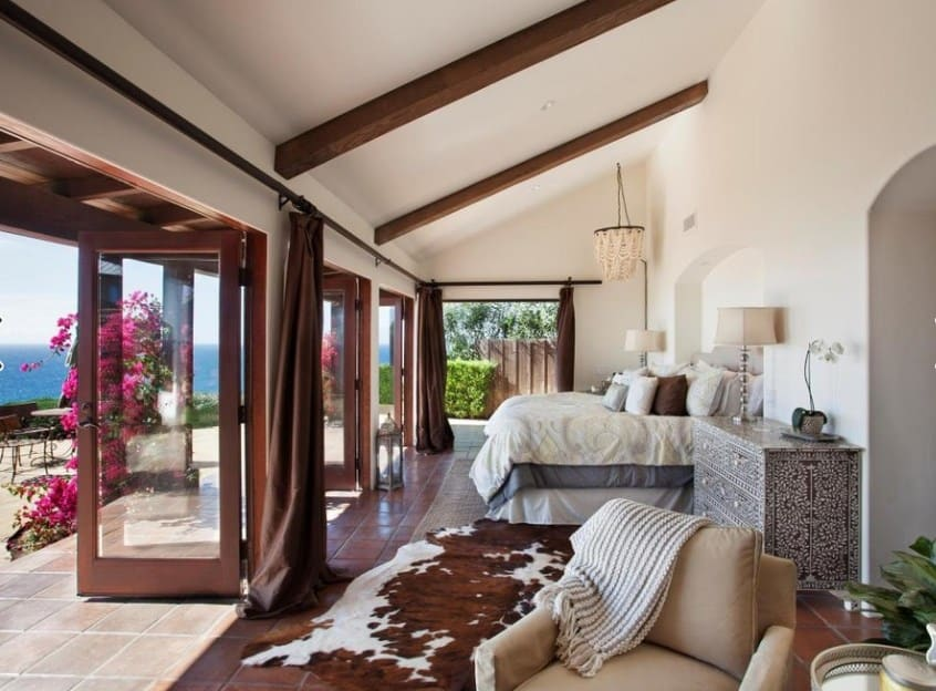 A long and narrow primary bedroom with a shed ceiling and tile flooring topped by a cowhide rug. It features charming furniture and French doors leading out to the patio with a serene outdoor view.