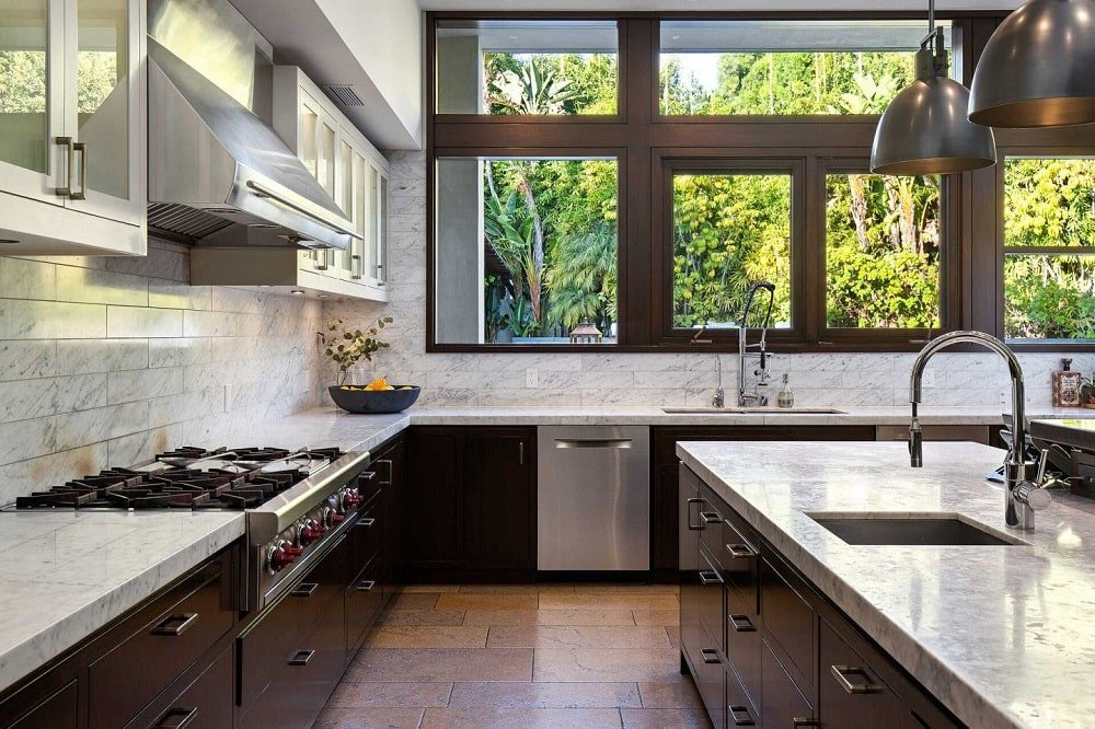 This is a close look at the kitchen that has dark modern cabinetry contrasted by the light tone of the countertops as well as the stainless steel appliances and fixtures. These are then brightened by the large window above the sink.