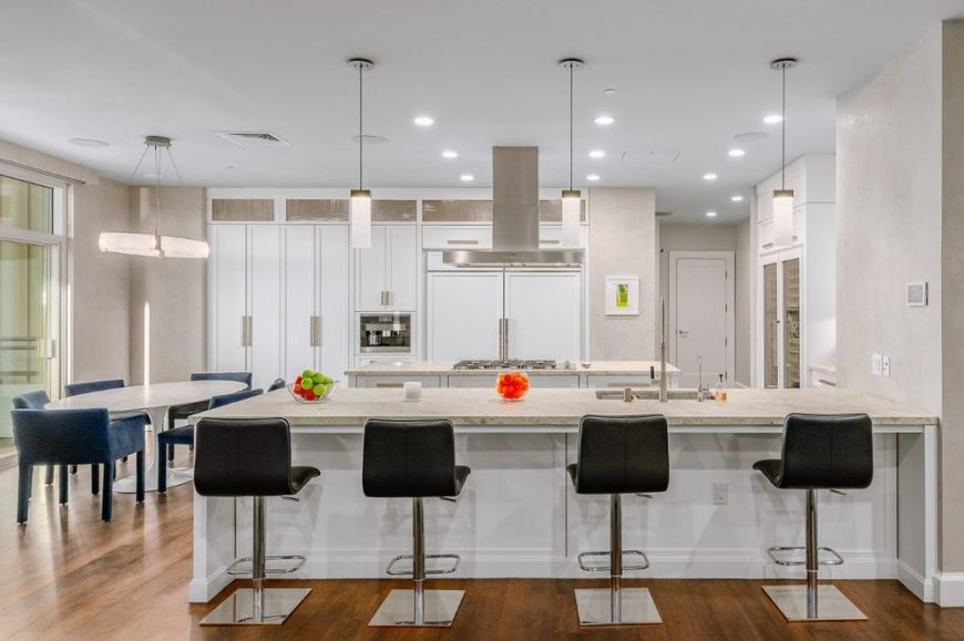 This is the bright and white eat-in kitchen that has a large peninsula that pairs with the white cabinetry and white walls. These are then contrasted by the black stools of the breakfast bar and the chairs of the informal dining area.