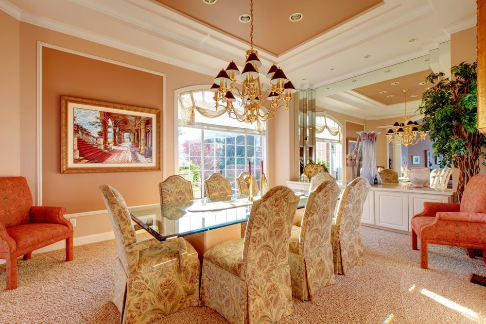 This luxury dining room is decorated with gorgeous painting and a gold chandelier that hung over the glass top dining table surrounded by skirted floral chairs. It has beige carpet flooring and a large arched window bringing an ample of natural light in.