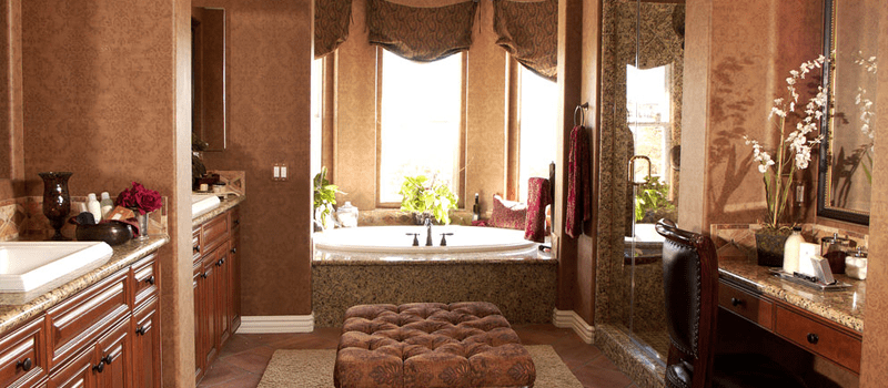 Mediterranean primary bathroom with gorgeous decorated brown walls along with two sink counters and a powder desk. There's a drop-in tub as well that looks elegant.