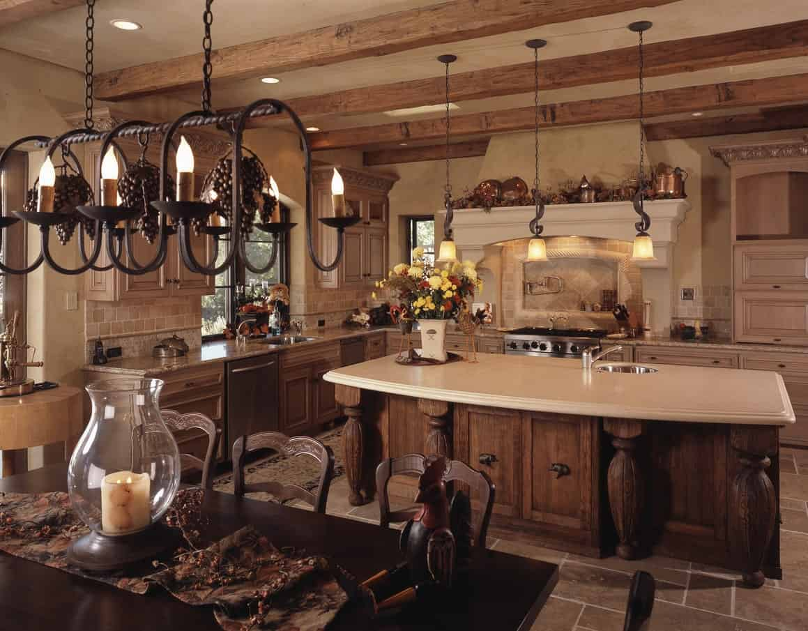 This is a large and homey Mediterranean-style kitchen with matching wooden cabinets and drawers on its kitchen island and L-shaped cabinetry lining the walls. These match with the exposed wooden beams of the ceiling that hangs a trip of wrought iron chandelier lights over the island.