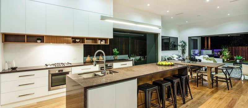 This medium-sized kitchen is part of a great room that also houses the dining area and the living room area on the far side. The wide and tall white ceiling has recessed lights blending well with the white modern cabinetry that houses the stainless steel stove-top oven. This is contrasted by a dark waterfall kitchen island.