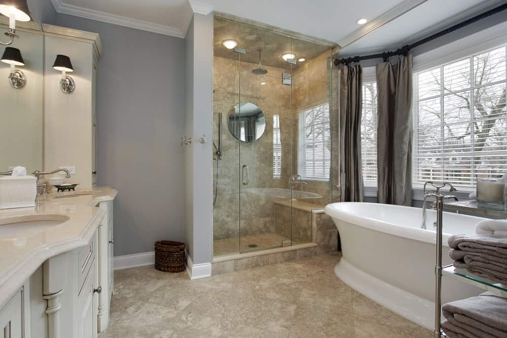 Medium-sized primary bathroom featuring gray walls and tiles floors. There's a sink counter with two sinks, lighted by wall sconces, together with a freestanding deep soaking tub and a walk-in shower room.