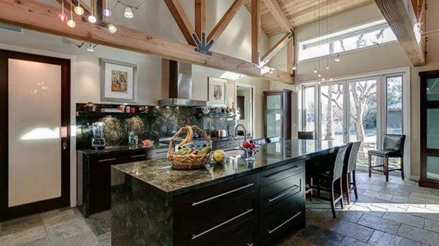The kitchen has dark cabinetry lining the walls that contrast the beige hues of the walls. This matches well with the large kitchen island under the exposed beams of the arched ceiling.