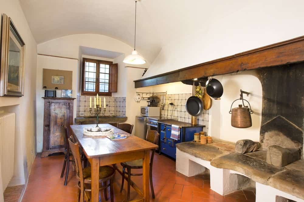 This is a rustic and romantic kitchen with a tall cove white ceiling to contrast the terracotta flooring and wooden table across from the cooking area serving as a kitchen island and informal dining area.