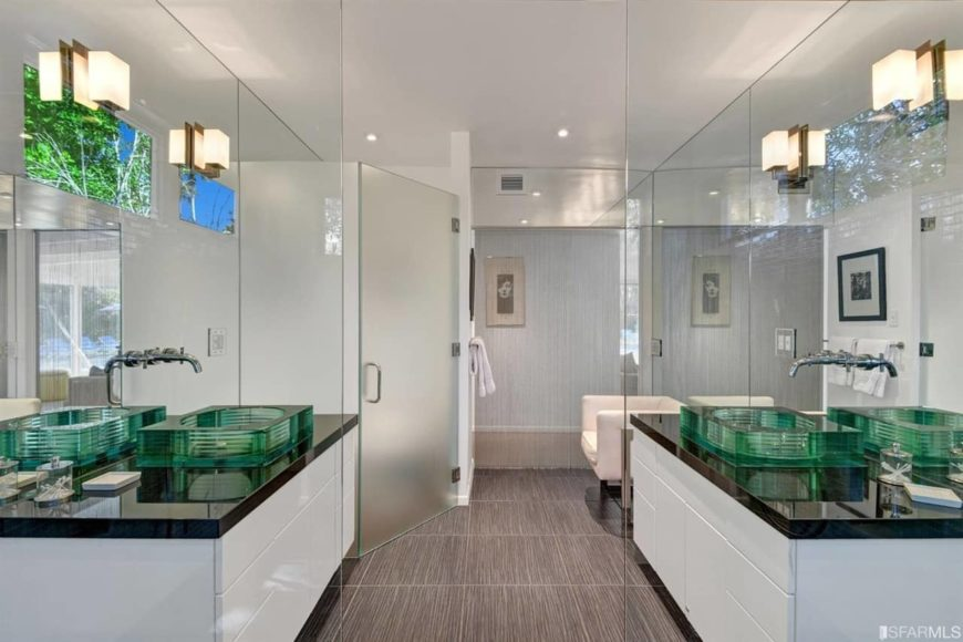 Mid-century modern master bathroom with stylish tiles flooring and a couple of attractive vessel sinks on floating vanity counters. There's a walk-in corner shower room as well.