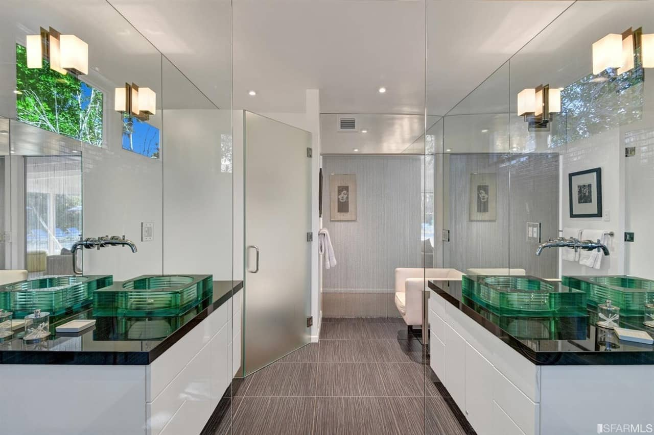 Mid-century modern primary bathroom with stylish tiles flooring and a couple of attractive vessel sinks on floating vanity counters. There's a walk-in corner shower room as well.