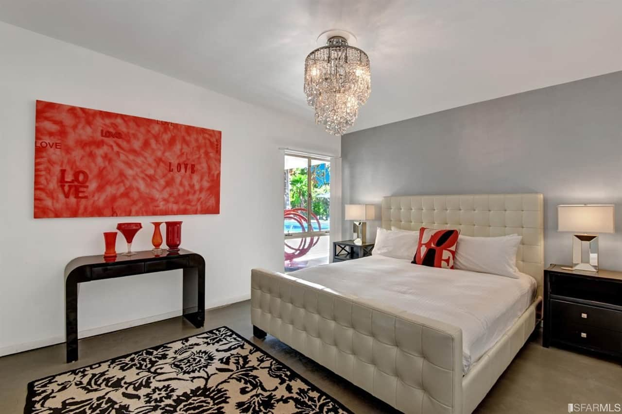 Red artwork and vases break the neutral color scheme in this mid-century primary bedroom boasting a white tufted bed contrasted by dark wood nightstands and a sleek console table. It is accompanied by a fancy crystal chandelier and a floral area rug that lays on the brown floor.