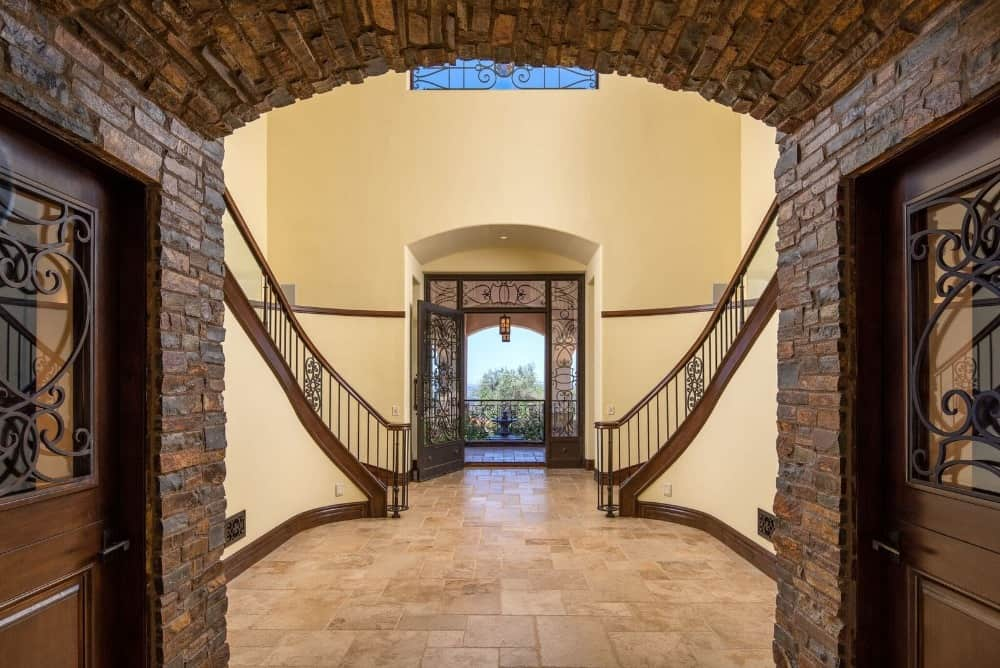 This entry foyer features beige tiles flooring and beige walls. There's a double staircase leading to the second floor as well.