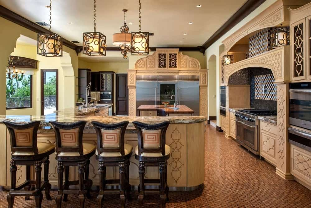 An elegant-looking kitchen featuring a center island and an L-shaped breakfast bar counter lighted by pendant lights.