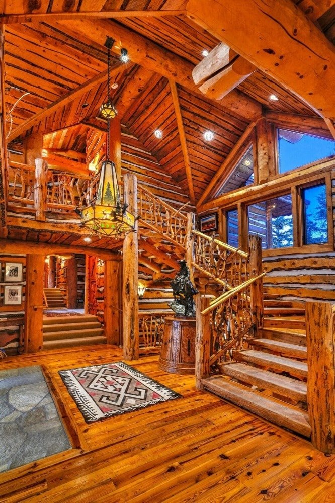 Entry hall of the house featuring hardwood flooring, hardwood walls, wooden staircase, and a tall wooden ceiling that hangs a unique decorative lighting. This is augmented by the glass walls beside the stairs.