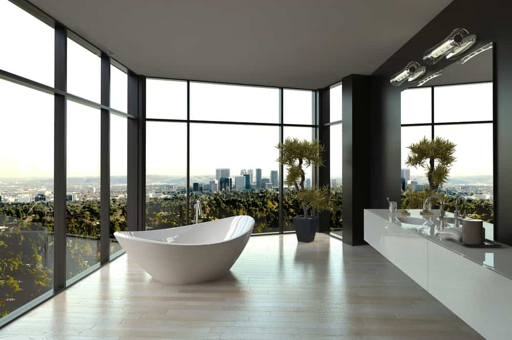 Luxury bathroom with glass walls, a freestanding tub, and floating vanity.