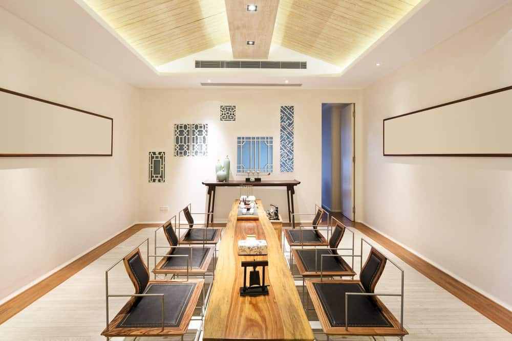 This dining room is furnished with a high console table and a stump dining table paired with modern black chairs. It has a luminous tray ceiling and pristine beige walls accented with gorgeous artworks.