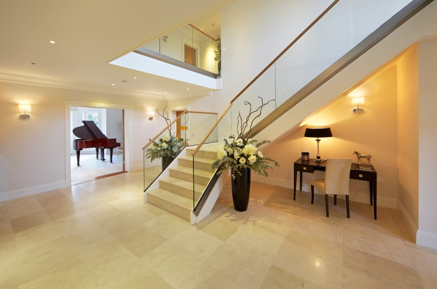 Spacious foyer area with beige tiles floors and white walls. It offers a quarter-turn staircase with glass railings.