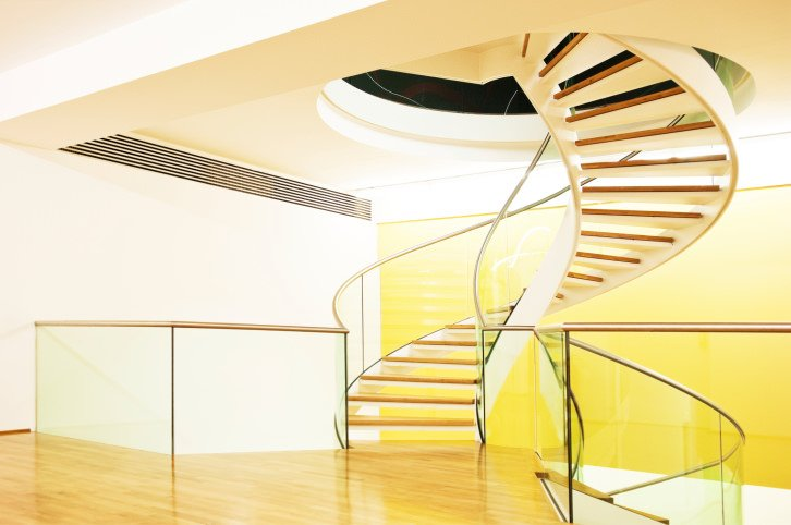 This home boasts a modern spiral staircase with glass railings. It looks absolutely stunning.
