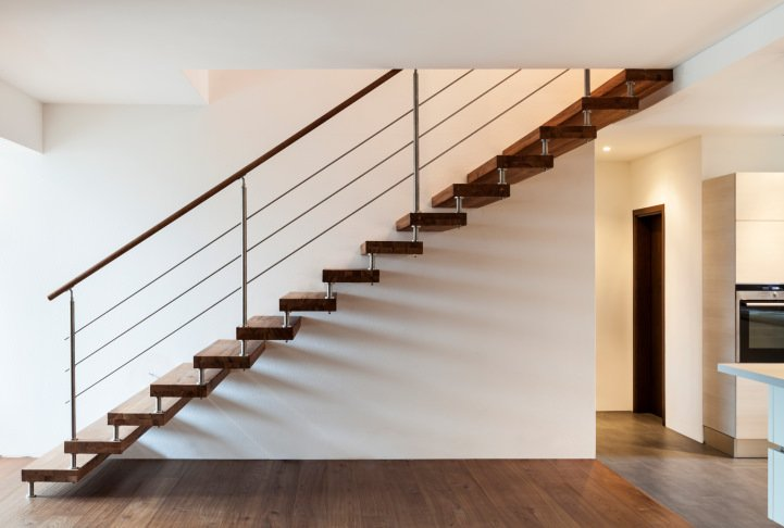 A minimalist home entry with hardwood floors and white walls. It also has a straight staircase with hardwood steps.