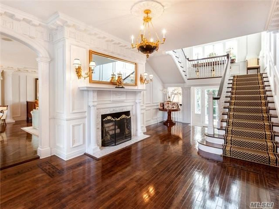 This is the grand foyer with a hardwood flooring that contrasts the white walls adorned with elegant designs and golden accents from the mirror above the fireplace and the golden chandelier.