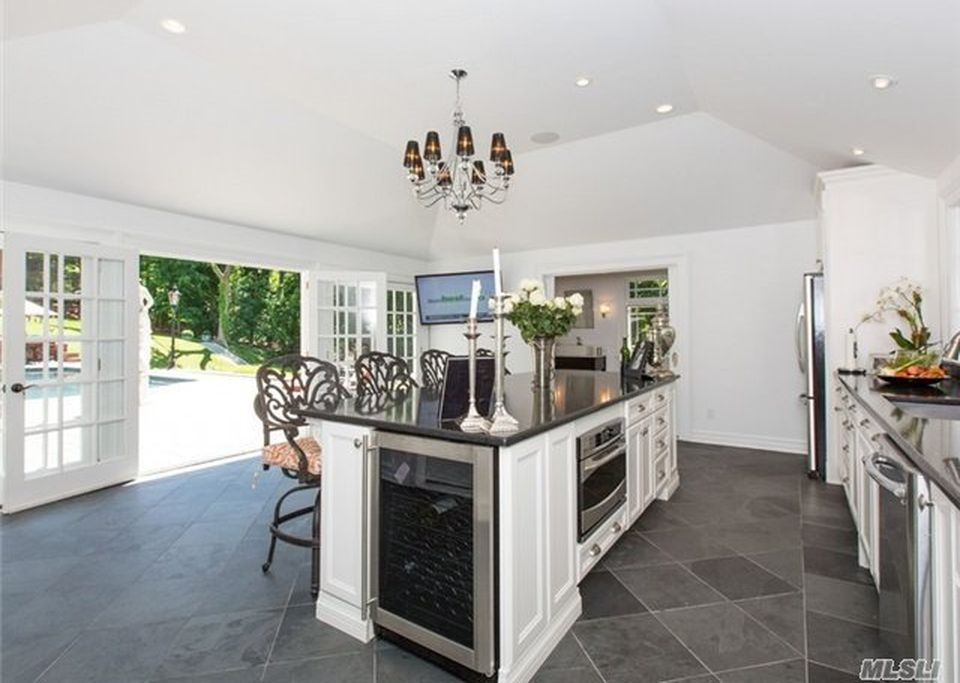 The kitchen has a large white kitchen island with a black countertop and a small chandelier above hanging from the white ceiling.