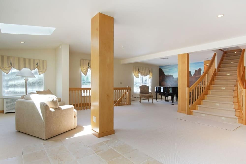 This is the spacious foyer of the house with bright flooring tiles and ceiling complemented by the wooden elements of the pillars and the staircase with a grand piano beside it.