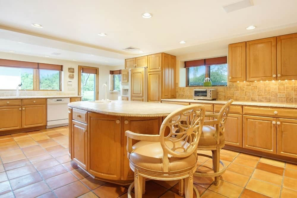 This is a charming kitchen with terracotta flooring tiles to match the light wooden cabinetry topped with beige countertops.