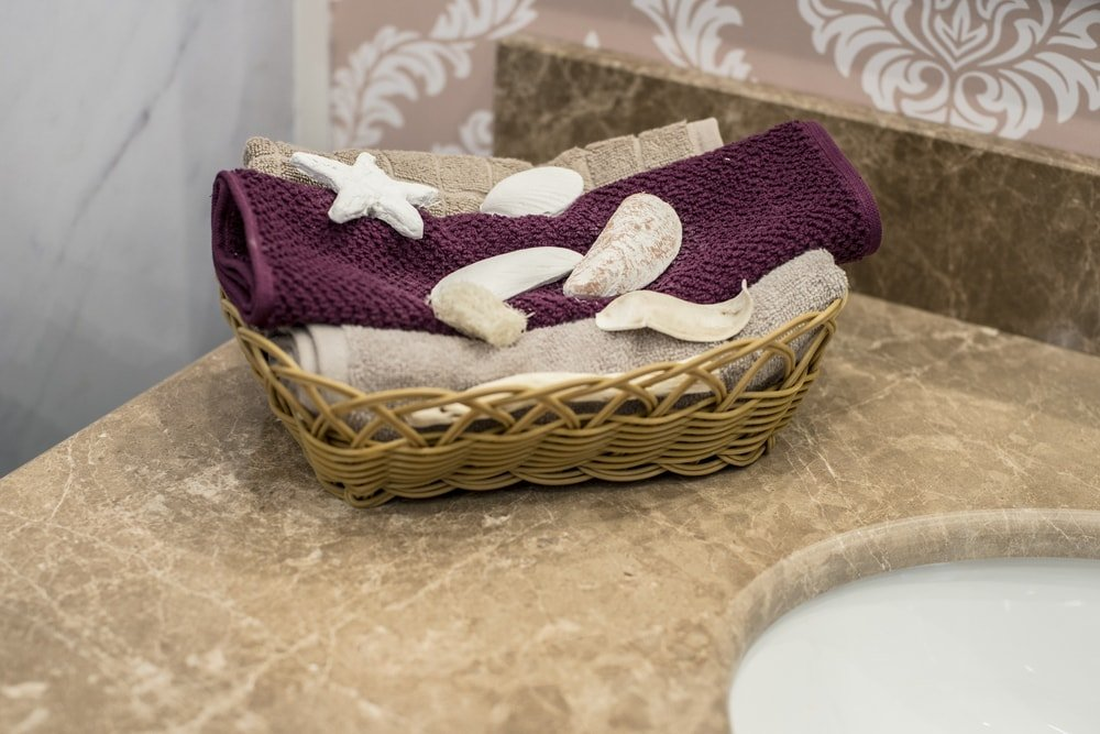 Folded face towels with a starfish and seashells placed in a basket on a sink.