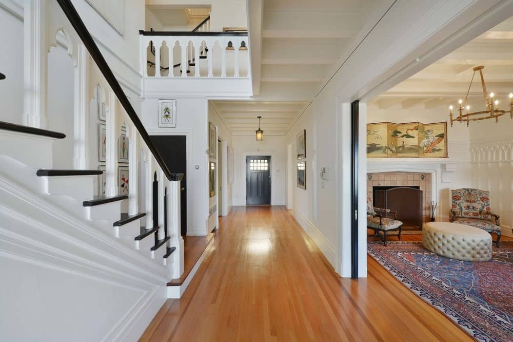 Entry hall leading to the home's living space. There's the home's staircase as well, featuring dark hardwood steps and handrail, along with white railings.