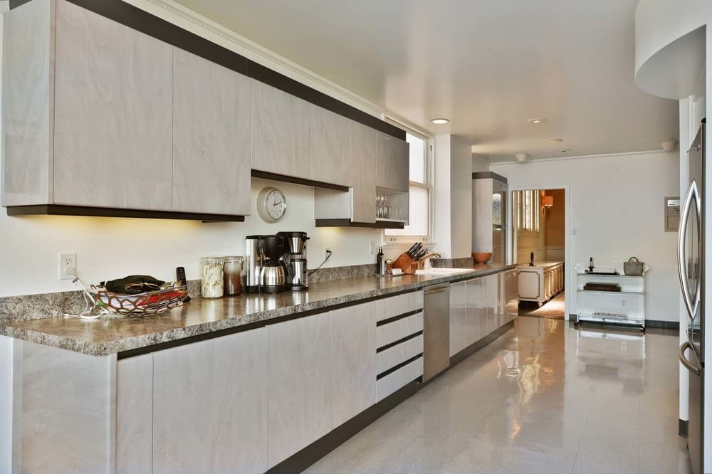 A single wall kitchen with a gorgeous kitchen countertop. The area also has tiles flooring and a regular ceiling.