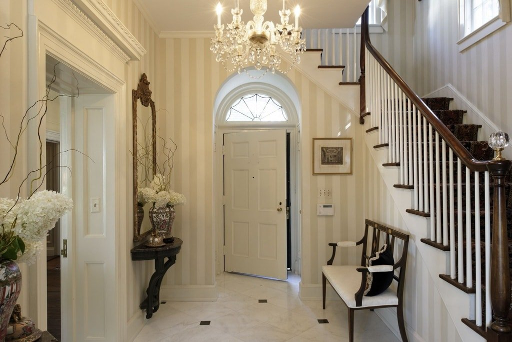Entry foyer with elegant walls and tiles flooring, lighted by a gorgeous chandelier.