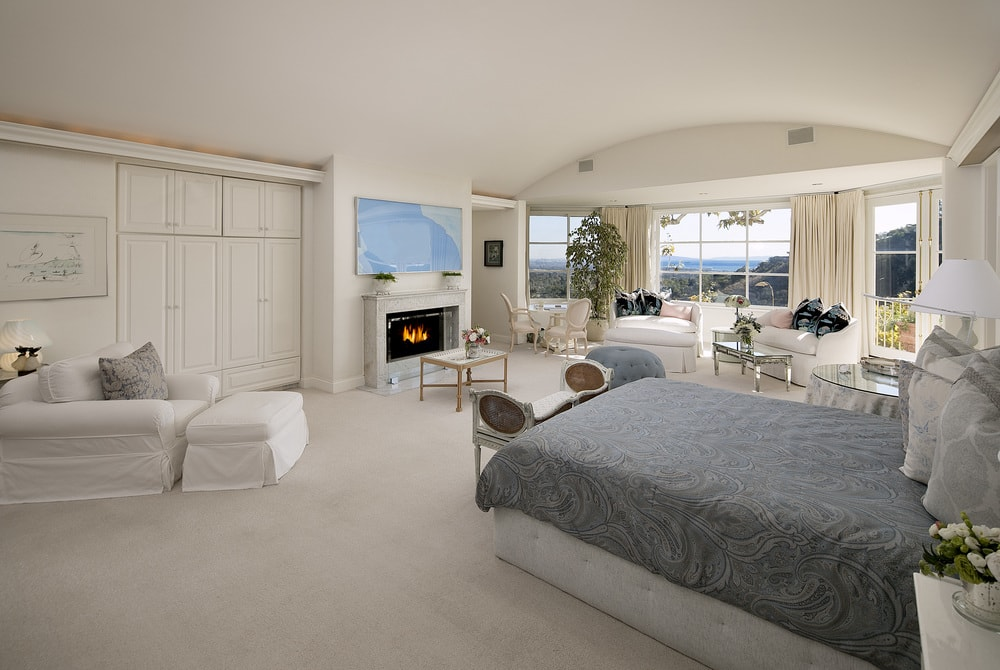 This primary bedroom has a lovely fireplace with a beige mantle that blends well with the beige walls and wide cove ceiling. These are then brightened by the wide windows at the sitting area.