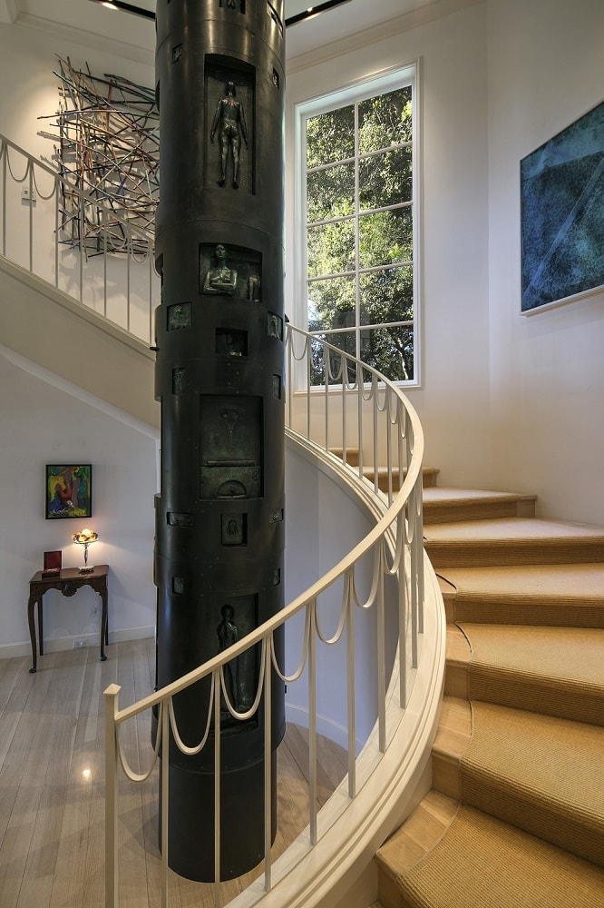 This is a view of the foyer that focuses on the curve staircase with thin intricate beige railings that stand out against the detailed black pillar in the middle with carvings.