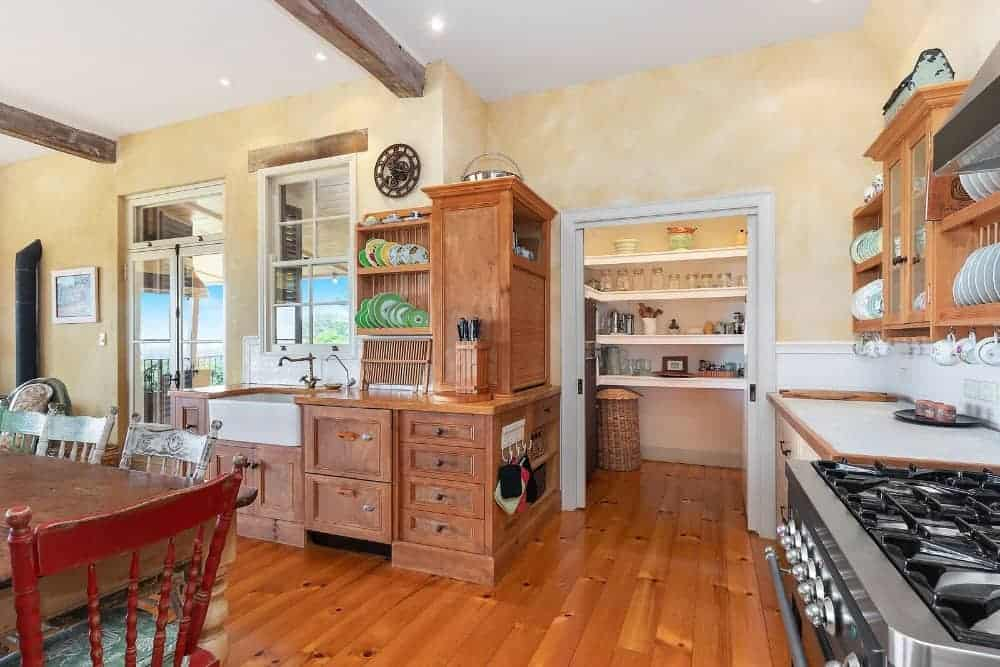 This kitchen offers brown cabinetry, kitchen drawers and built-in shelving, along with a pantry room on the side.