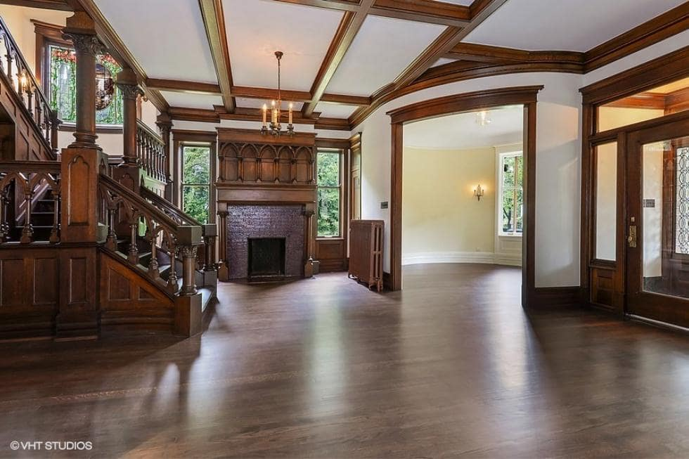 Upon entry of the house, you are welcomed by this foyer with its own fireplace near the wooden stairs these are then complemented by a coffered ceiling.