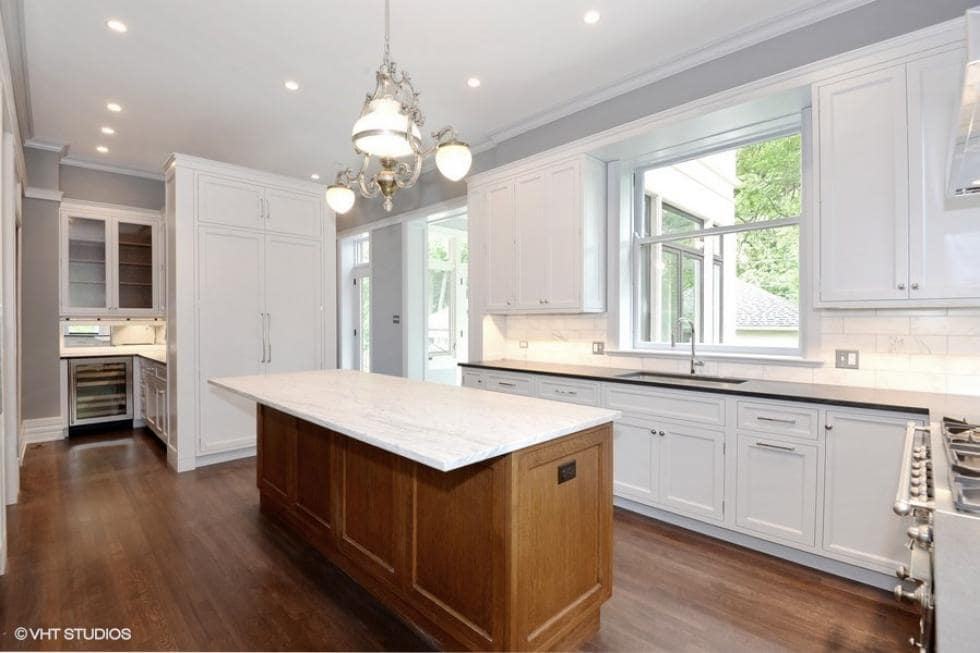 The kitchen has a kitchen island with wooden cabinetry that matches the floor. These are then contrasted by the surrounding white shaker cabinets, white countertops and the white walls.