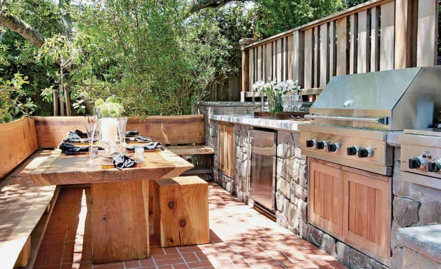 This is a cozy outdoor kitchen with a dining nook of bare wooden dining table, built-in L-shaped bench and small stools that go quite well with the terracotta flooring. This also complements the textured stone structure that houses the stainless steel appliances.