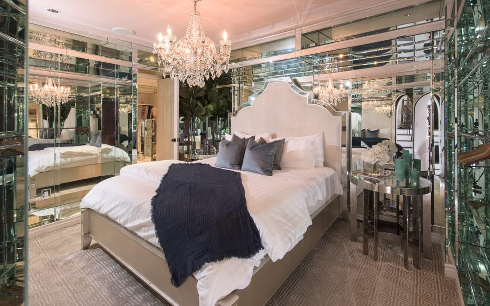 A bedroom suite with glass walls and a luxurious bed set lighted by a glamorous chandelier.