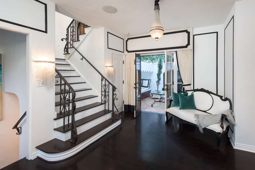 A small entry hall with dark hardwood floors and decorated black and white walls.