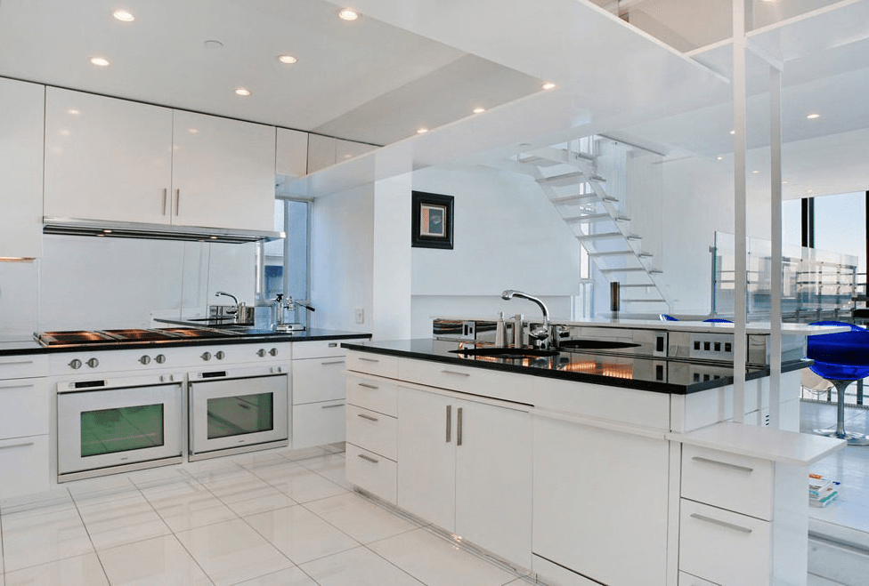 The kitchen has bright white cabinetry that matches the walls and ceiling. These are then contrasted by the black countertops.