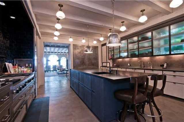 The large kitchen has a large dark kitchen island topped with a pendant light that hangs from a beamed beige ceiling with multiple flush-mount lighting.