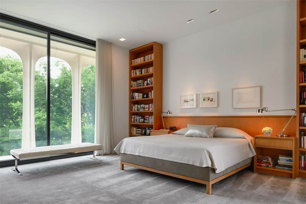 The large bedroom has a wooden bed attached to a large wooden structure that extends from the wooden headboard to the bookshelves on either side.