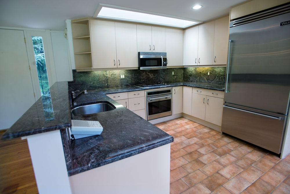 This is the small U-shaped kitchen with beige cabinetry contrasted by the black marble countertop and backsplash that makes the stainless steel appliances stand out.