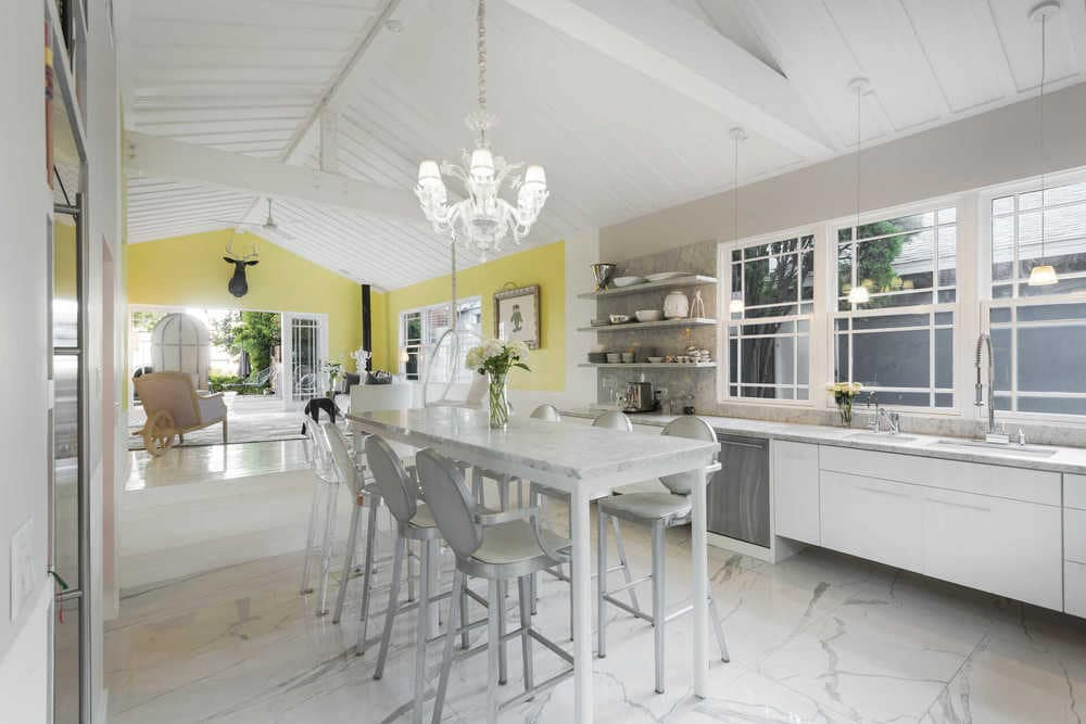 This is the kitchen of the house that has bright white marble flooring, white walls, a white cathedral ceiling that hangs a white decorative chandelier over the tall white table.
