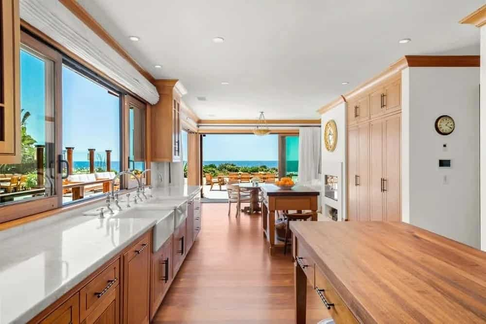 This is a close look at the kitchen with an abundance of wooden elements and cabinetry to match the hardwood flooring.