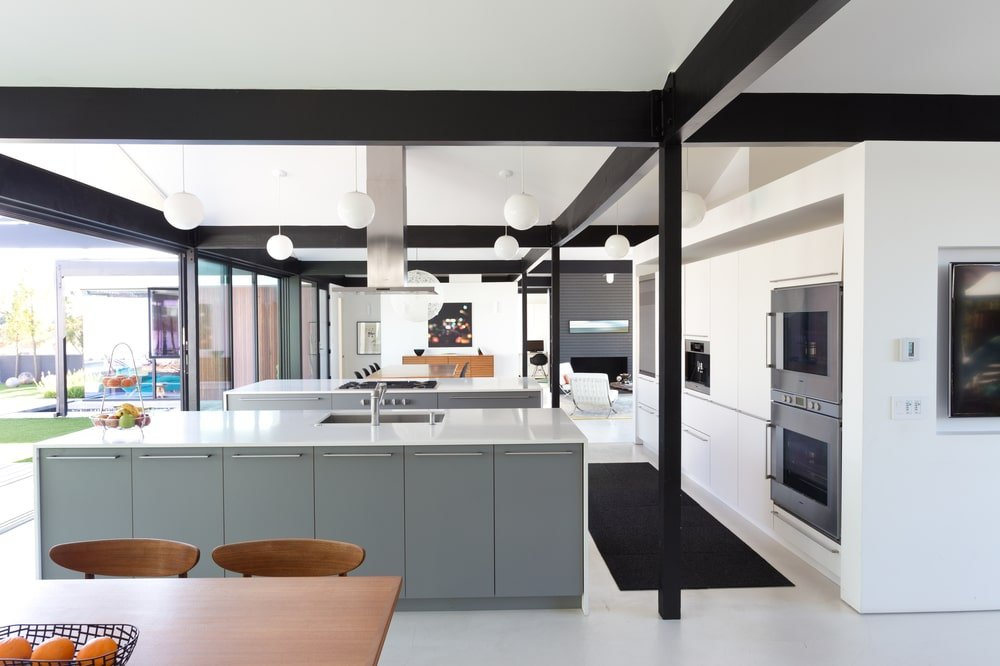 The kitchen has light gray kitchen islands that are contrasted by the black metal beams that run the ceiling that also extend to the pillars.