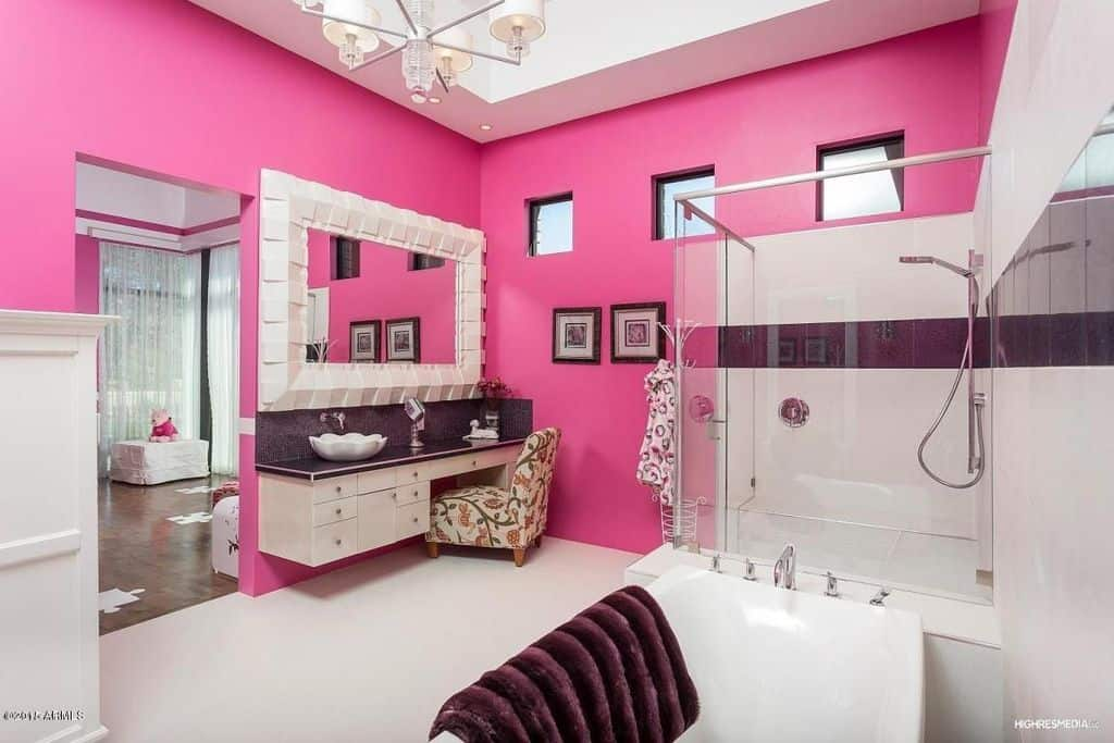 A primary suite offering a primary bathroom surrounded by pink walls. It has a walk-in shower area, a freestanding tub, a floating vanity with a vessel sink and a powder desk and a ceiling with a lovely chandelier lighting.