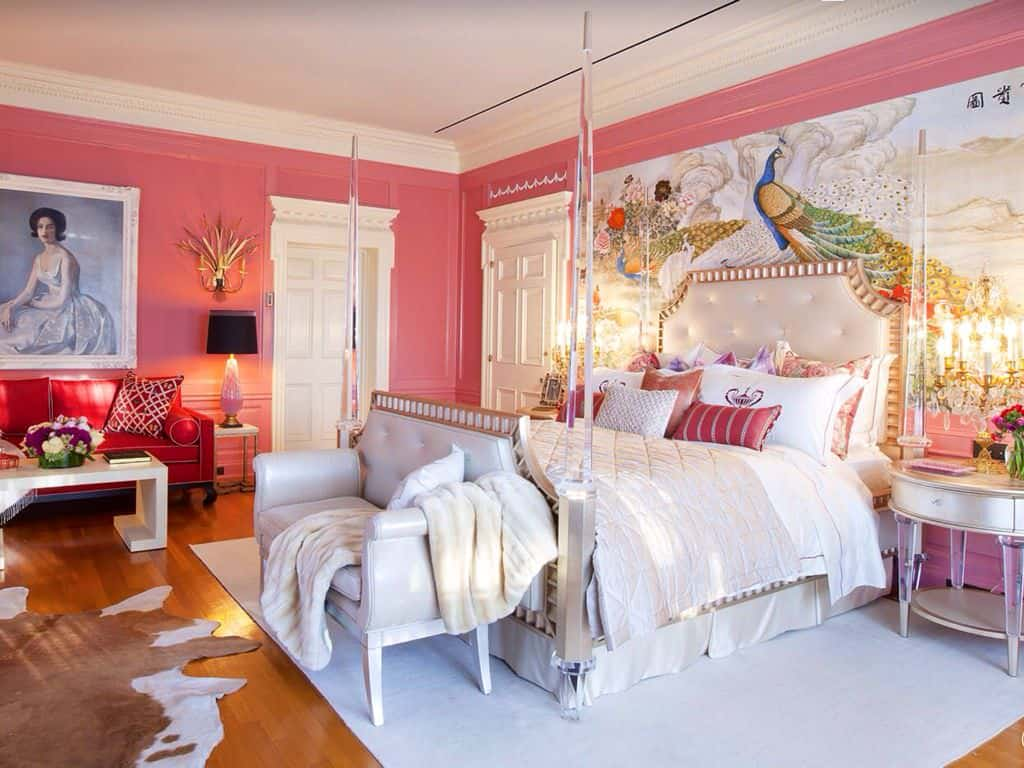Charming primary bedroom with natural hardwood flooring and pink wainscoted walls accented with a lovely portrait and a large peacock artwork. It showcases a glass four-poster bed and elegant seats complemented by a cowhide rug.